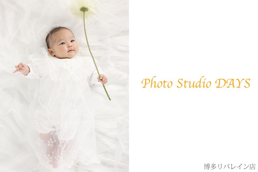 お花を片手に微笑む赤ちゃん