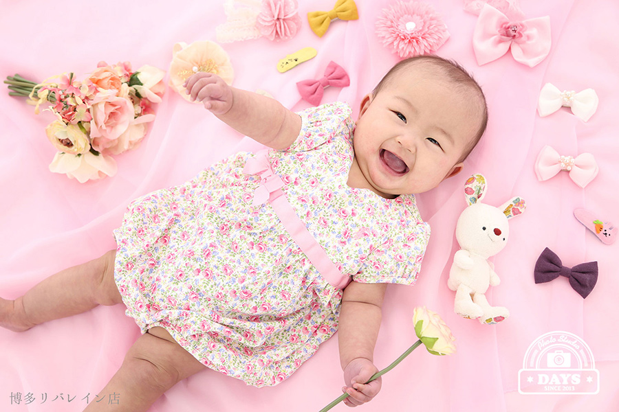 ニコニコ笑顔で寝転ぶ赤ちゃんの写真