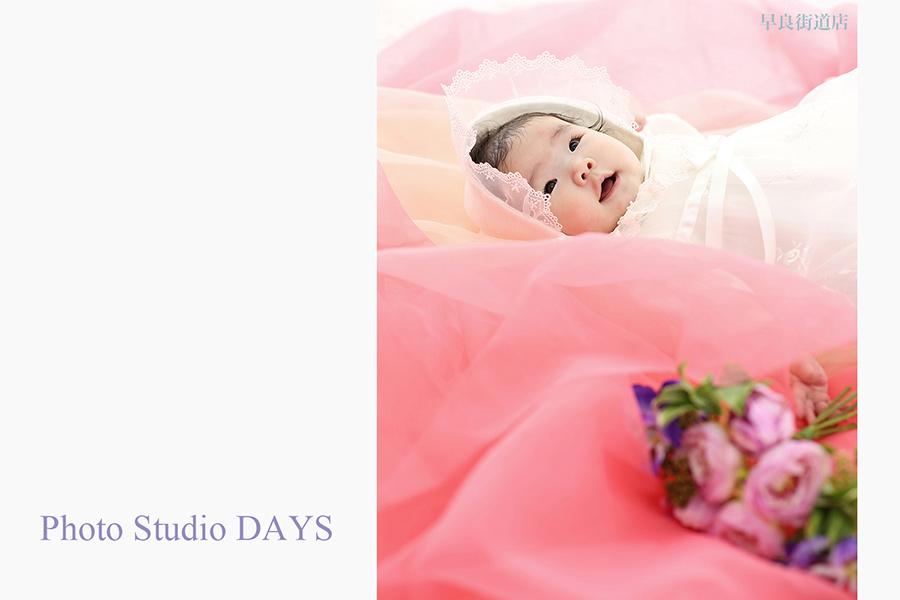 ピンクのオーガンジーに包まれる4ヶ月の女の子の写真