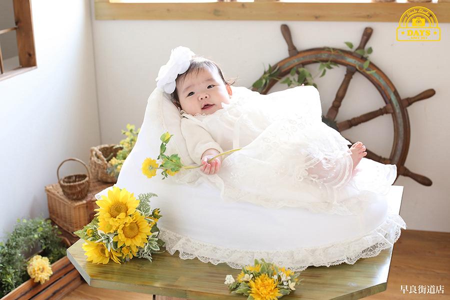 自然光の中黄色のお花を握った赤ちゃんの写真