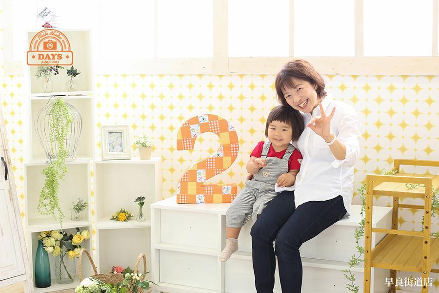 2歳イエーイとカメラに向かって2のポーズを見せてくれるママと娘の写真