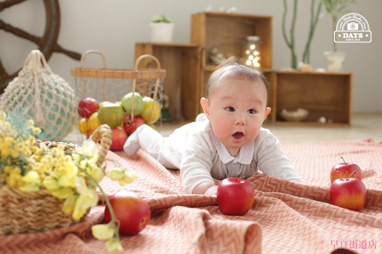 うつ伏せでびっくり顔の自然な6か月の赤ちゃん撮影