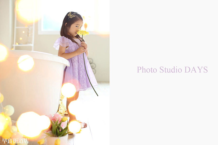 キラキラ電飾の中ドレス姿でお花を持つ女の子の写真