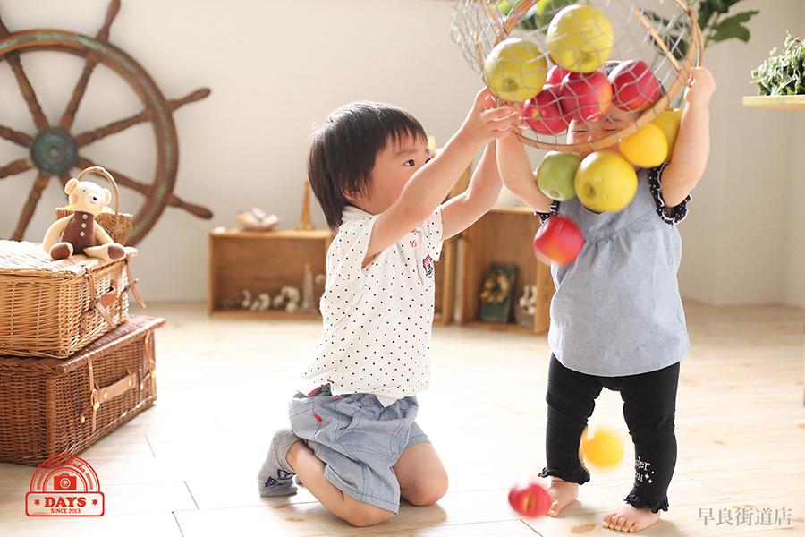 リンゴで遊ぶ兄弟写真