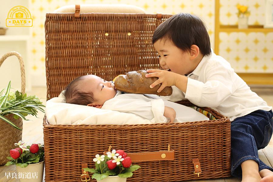 赤ちゃんにパンを食べさせるお兄ちゃん自然な兄弟写真