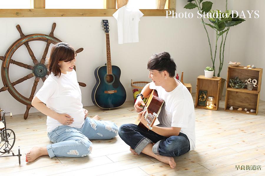 ママと赤ちゃんにギターを弾いてあげるパパ自然なマタニティフォト